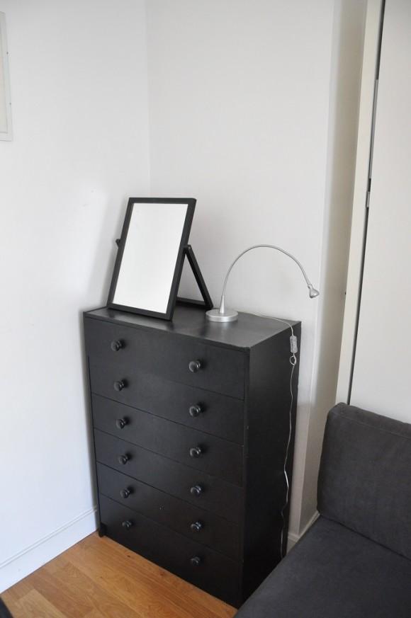 Um armário com gavetas e um espelho