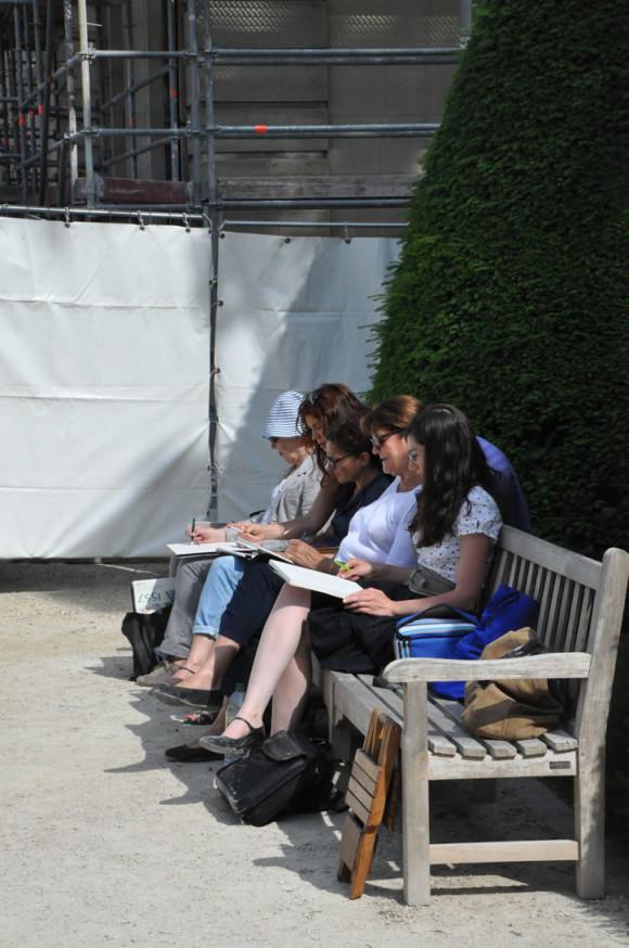 Tinha um grupo de estudantes reproduzindo no caderno as esculturas do jardim
